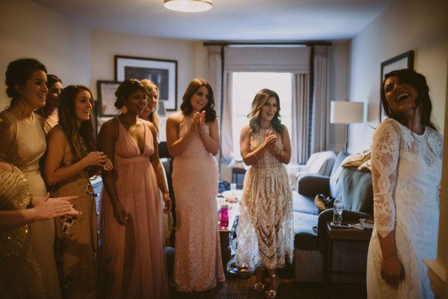 Bride shows off dress to bridesmaids