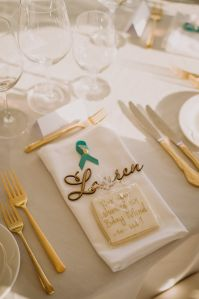place setting with gold cutlery and white napkin with wooden names