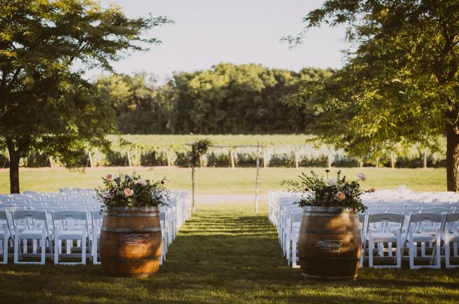 ceremony set up with wine barrels and florals to start aisle and birch wood arbour with vineyard as backdrop
