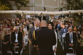 bride and groom stand before guests during ceremony