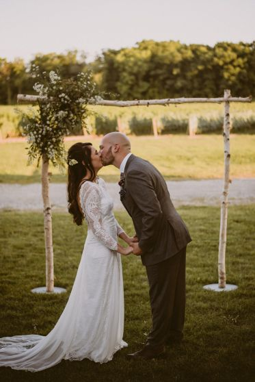 bride and groom first kiss in vineyard