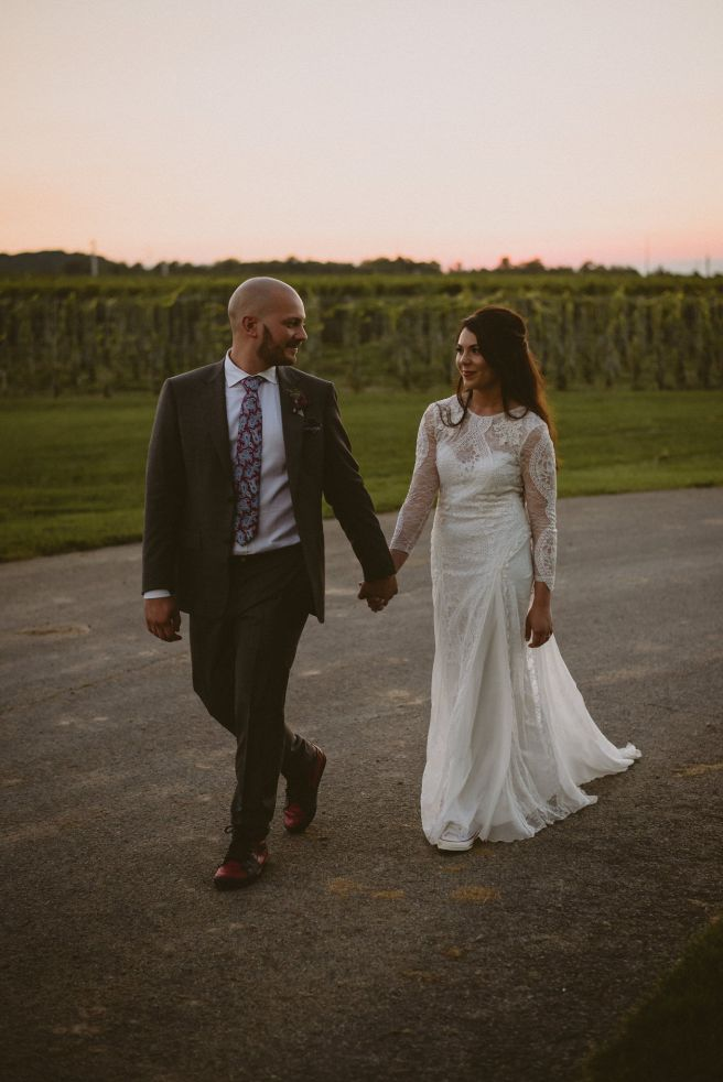 bride and groom walking hand in hand during sunset in vineyard