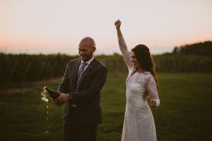 bride and groom pop champagne in vineyard