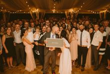 bride and groom with all guests on dance floor
