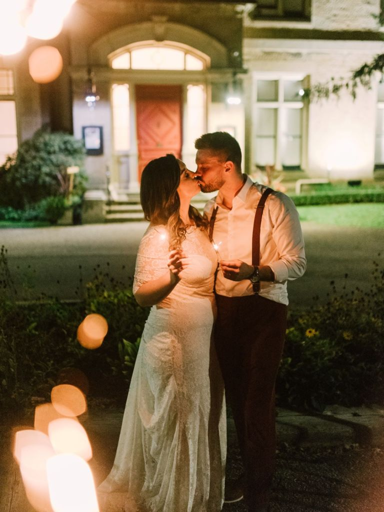 Bride and groom kissing outside of Rodman Ha;;