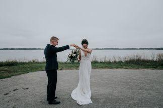 Bride & groom dancing by lake