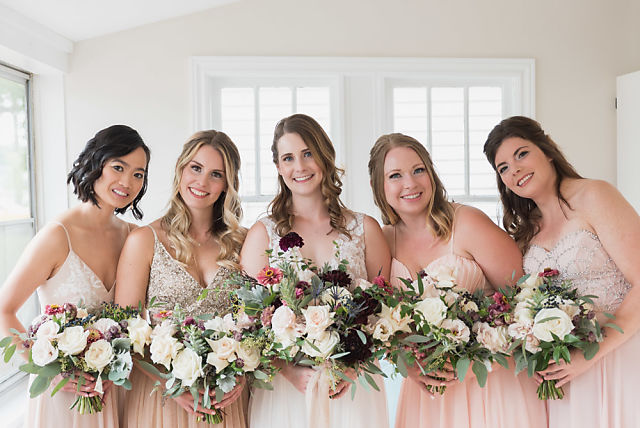 Bride and bridesmaids pose together before wedding ceremony