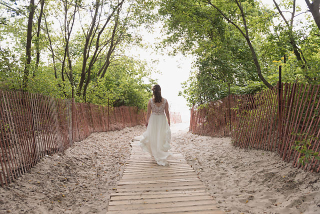 bride walking down beach path to first look