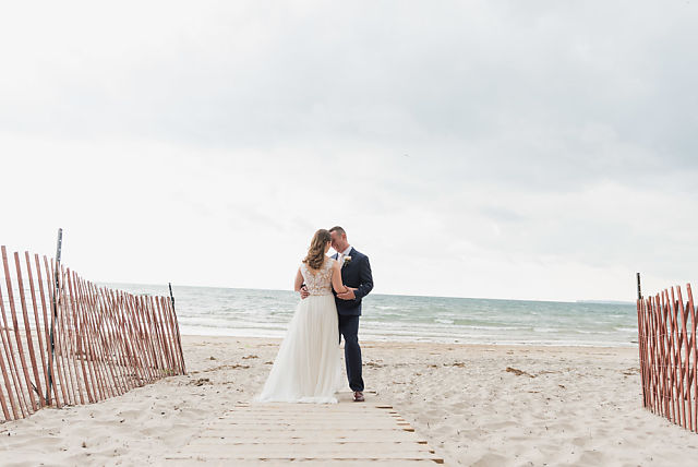bride and groom pose on beach