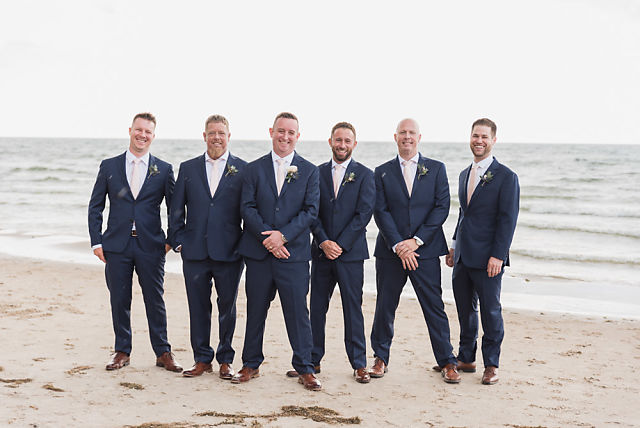 groom and groomsmen pose on beach