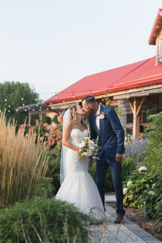 bride and groom kiss in gardens at Stonewall Estates Winery
