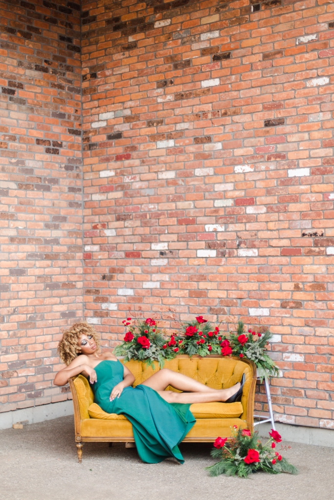 Model on lounge set surrounded by red flowers at The Hare Winery in Niagara-on-the-Lake