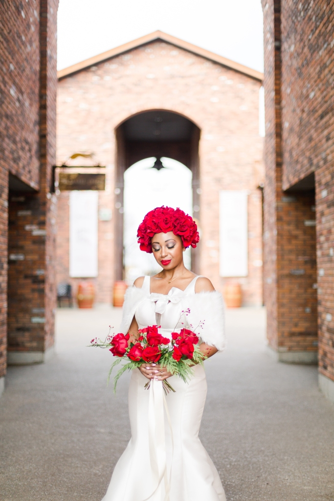 Bride with Rose Floral Crown holding red bridal bouquet at winery in Niagara-on-the-Lake