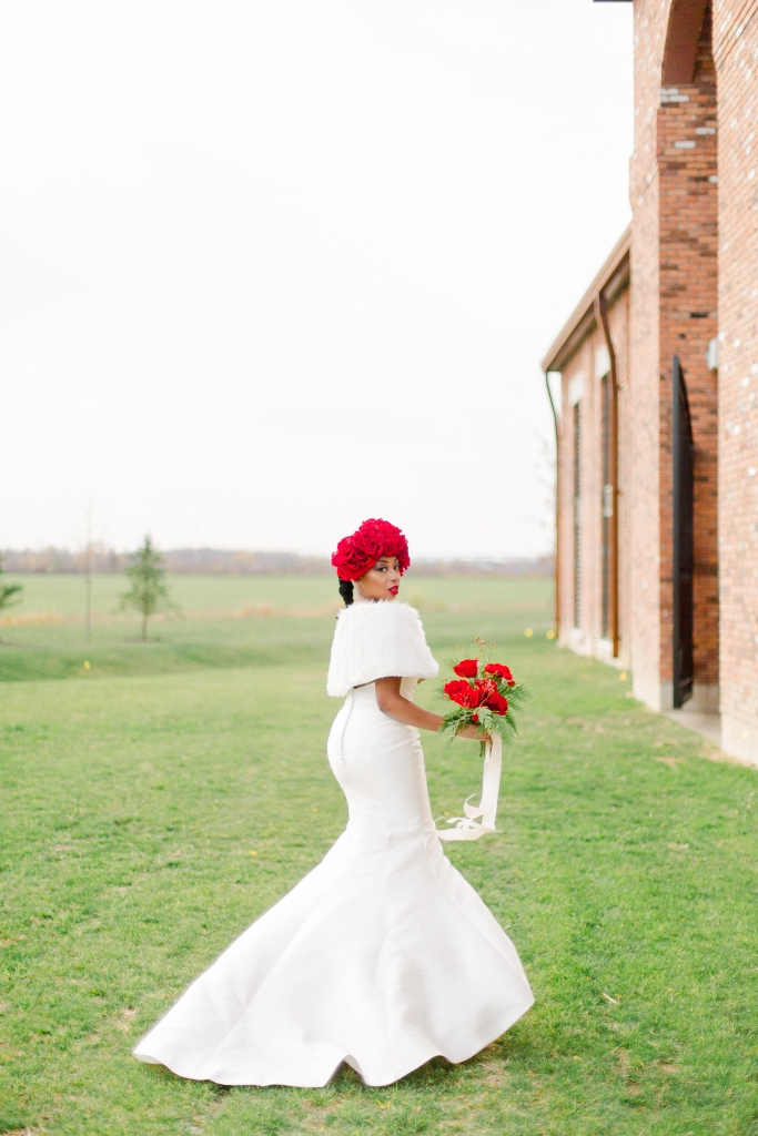 Bride in field at The Hare Winery in Niagara-on-the-Lake holding red bridal bouquet