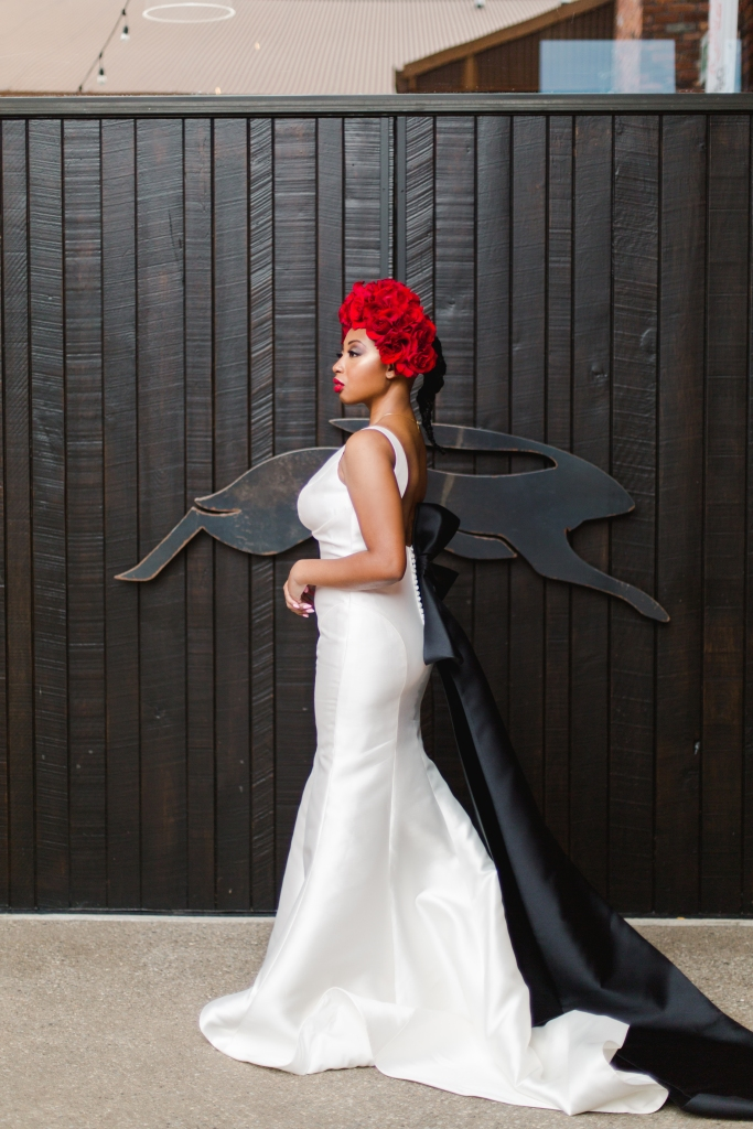 bride with red rose floral crown standing infront of Black door to winery in Niagara-on-the-Lake
