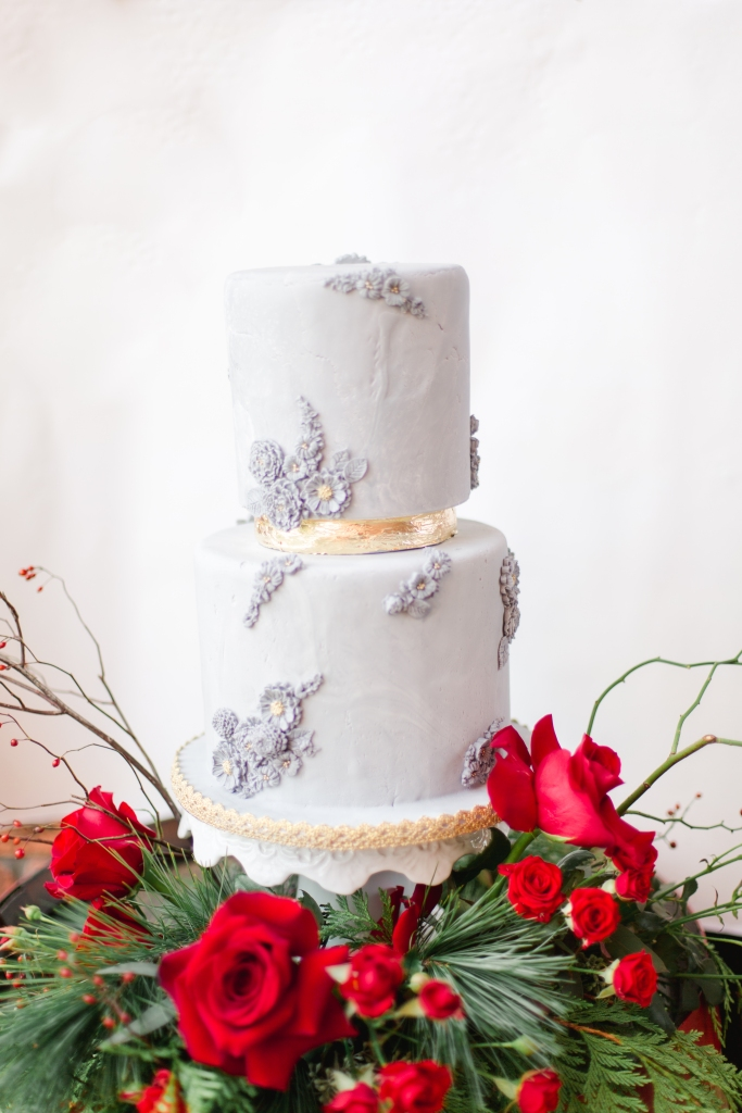 Grey wedding cake with red and green florals around botthm