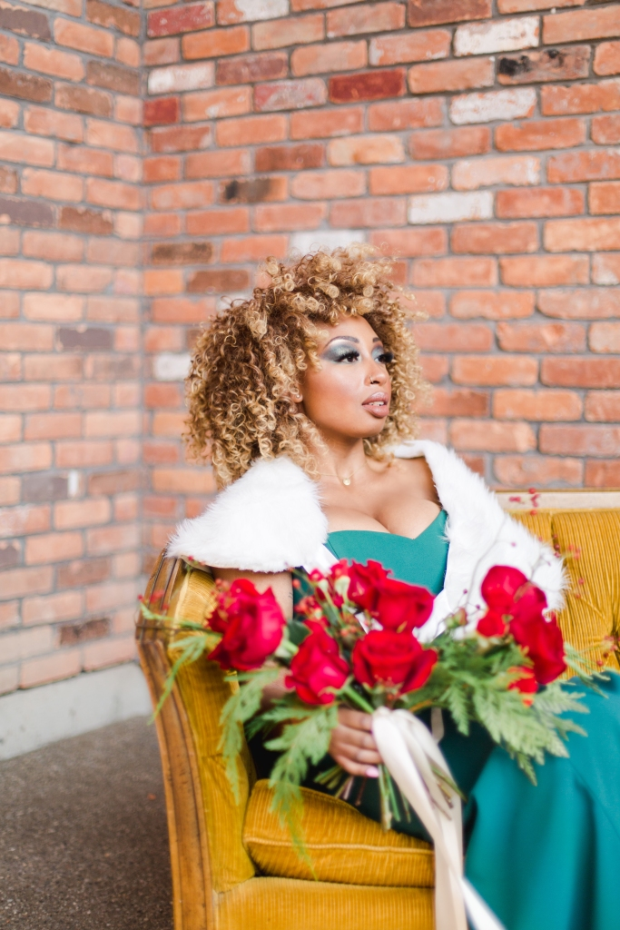 model in green dress and white fur wrap on yellow couch with red bridal bouquet