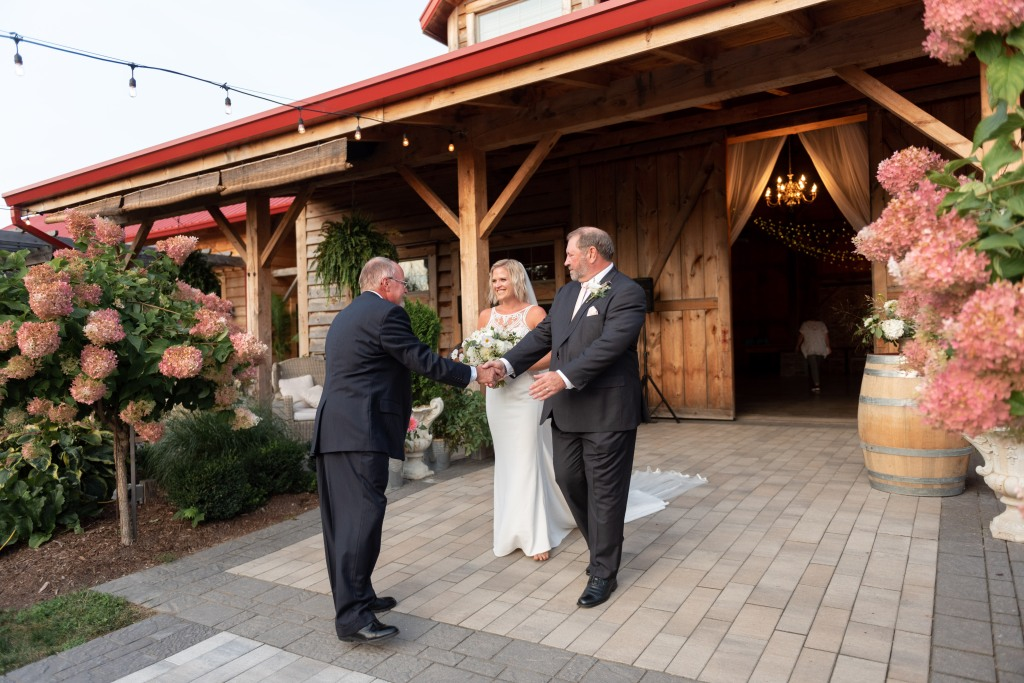 bride being walked down aisle by stepdad and handed over to dad
