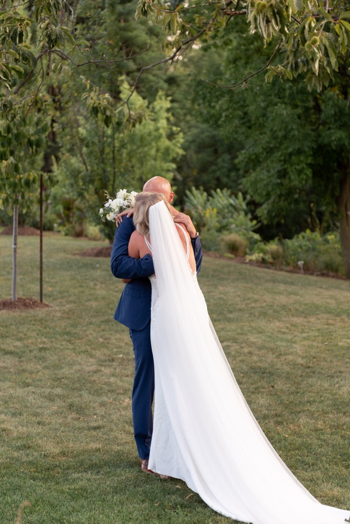 bride and groom hug during first look at Stonewall Estates in Niagara