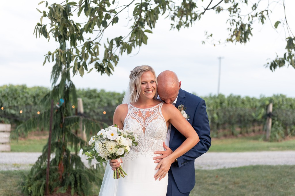 groom kissing brides shoulder at Stonewall Estates in Niagara