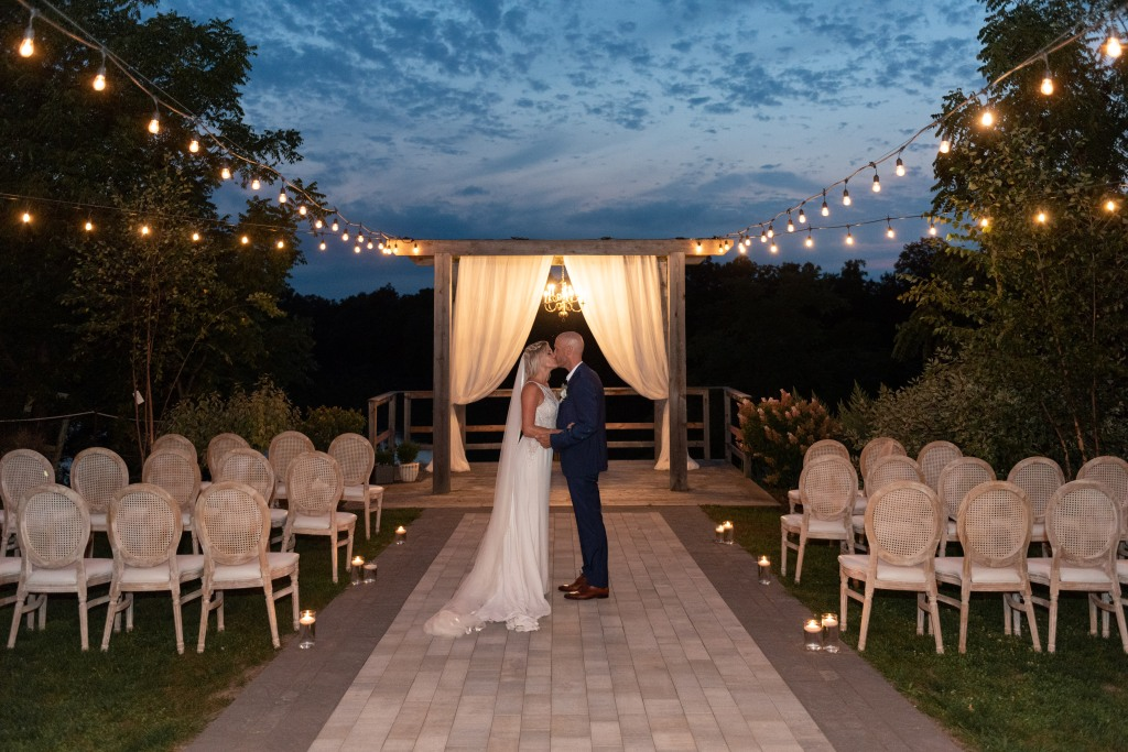 bride and groom share a kiss at dusk