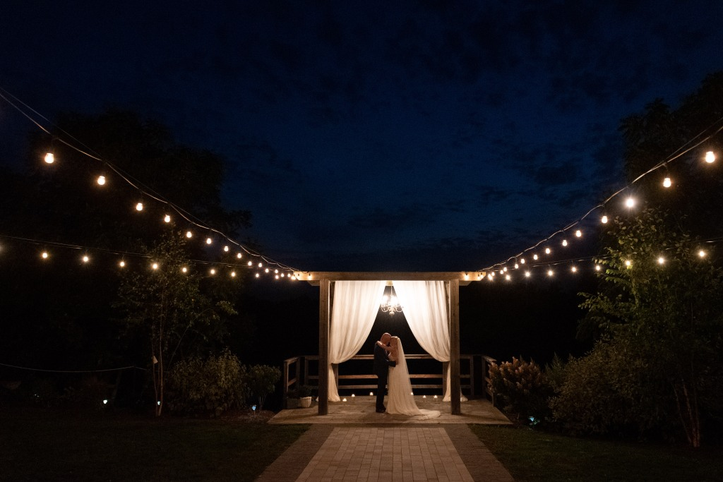 Bride and groom share first dance alone light up by candles and string lights at night at Stonewall Estates in Niagara