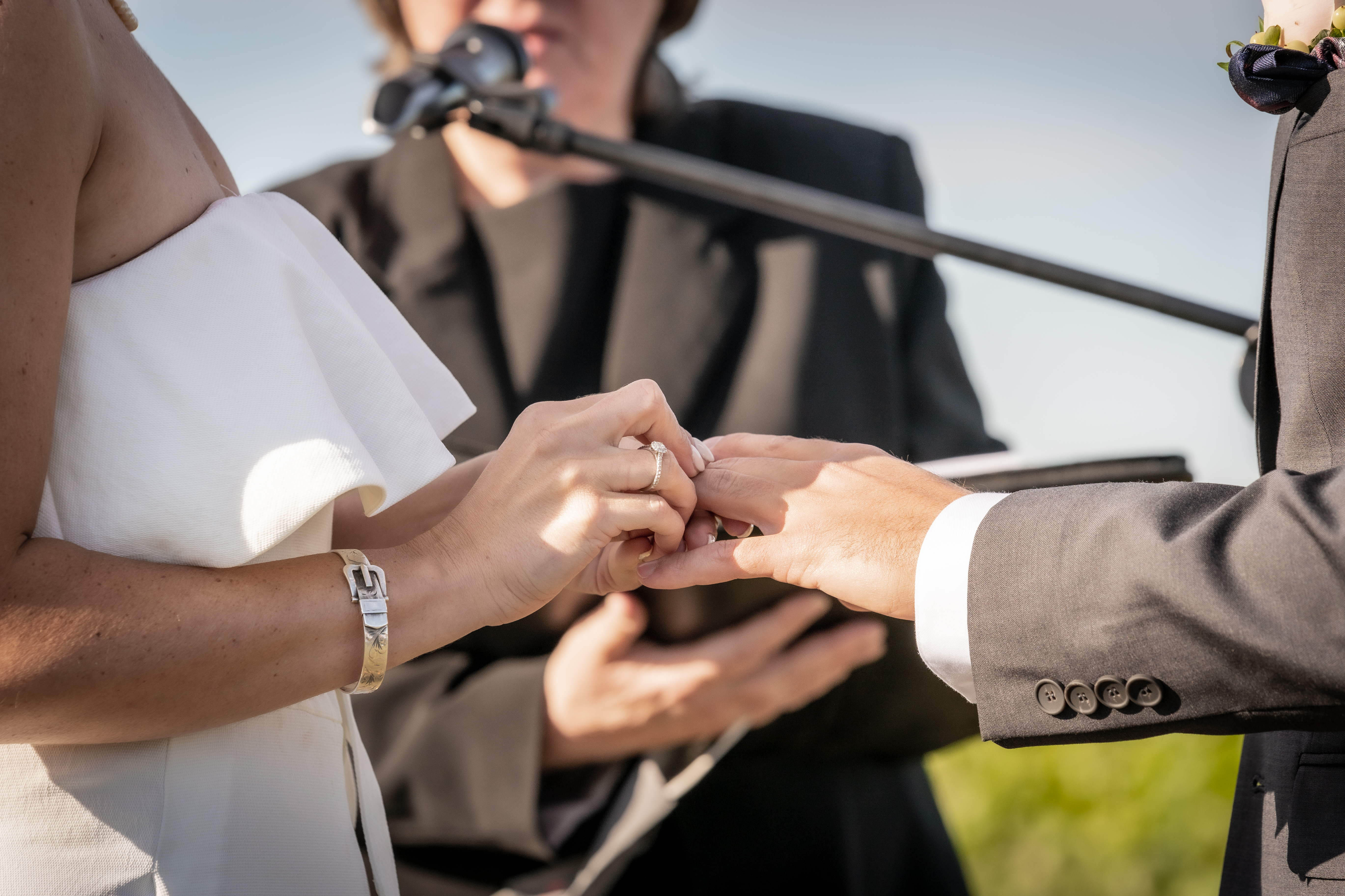 close up of bride putting ring on groom