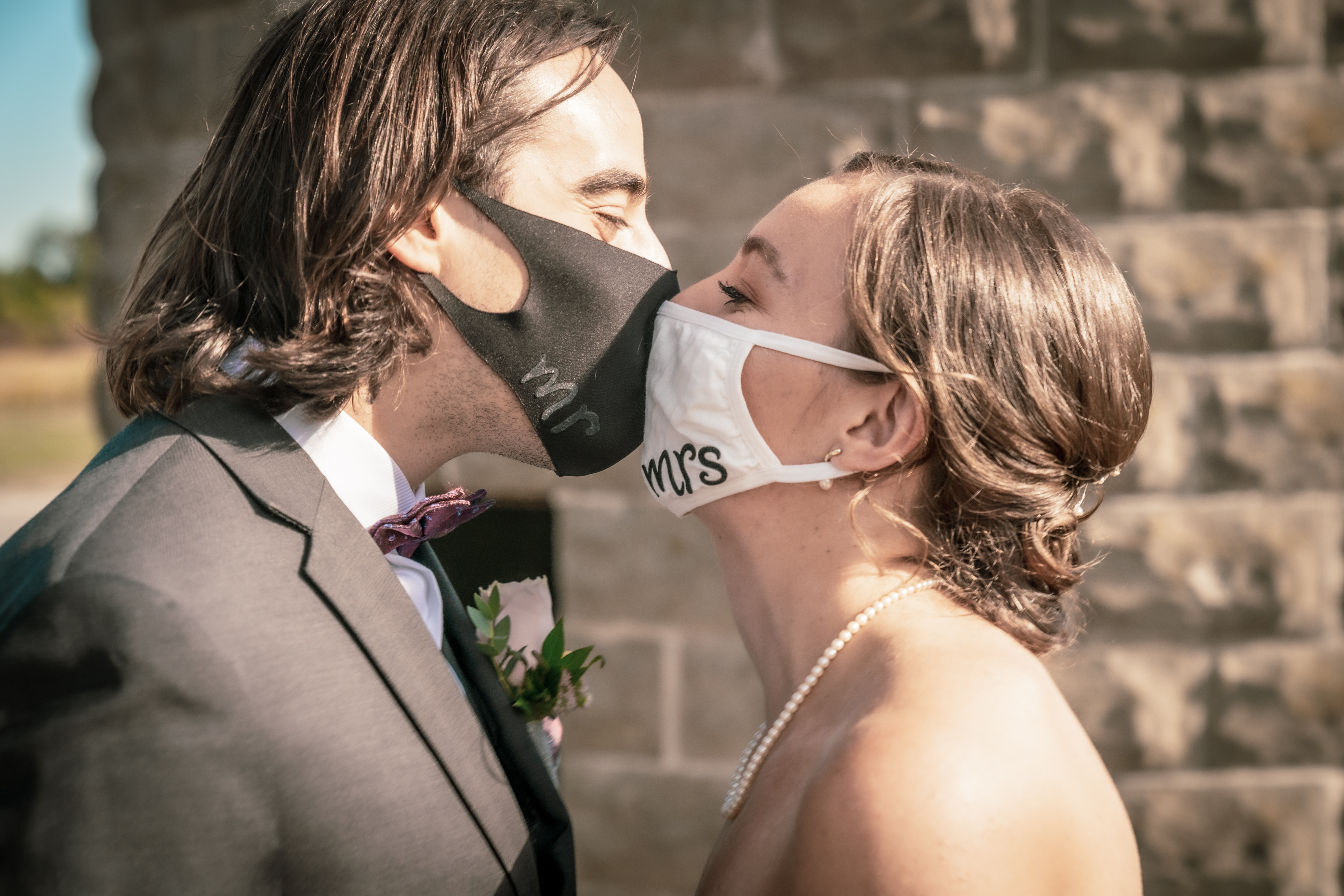 Bride and groom kissing with face masks on that read Mr. and Mrs.