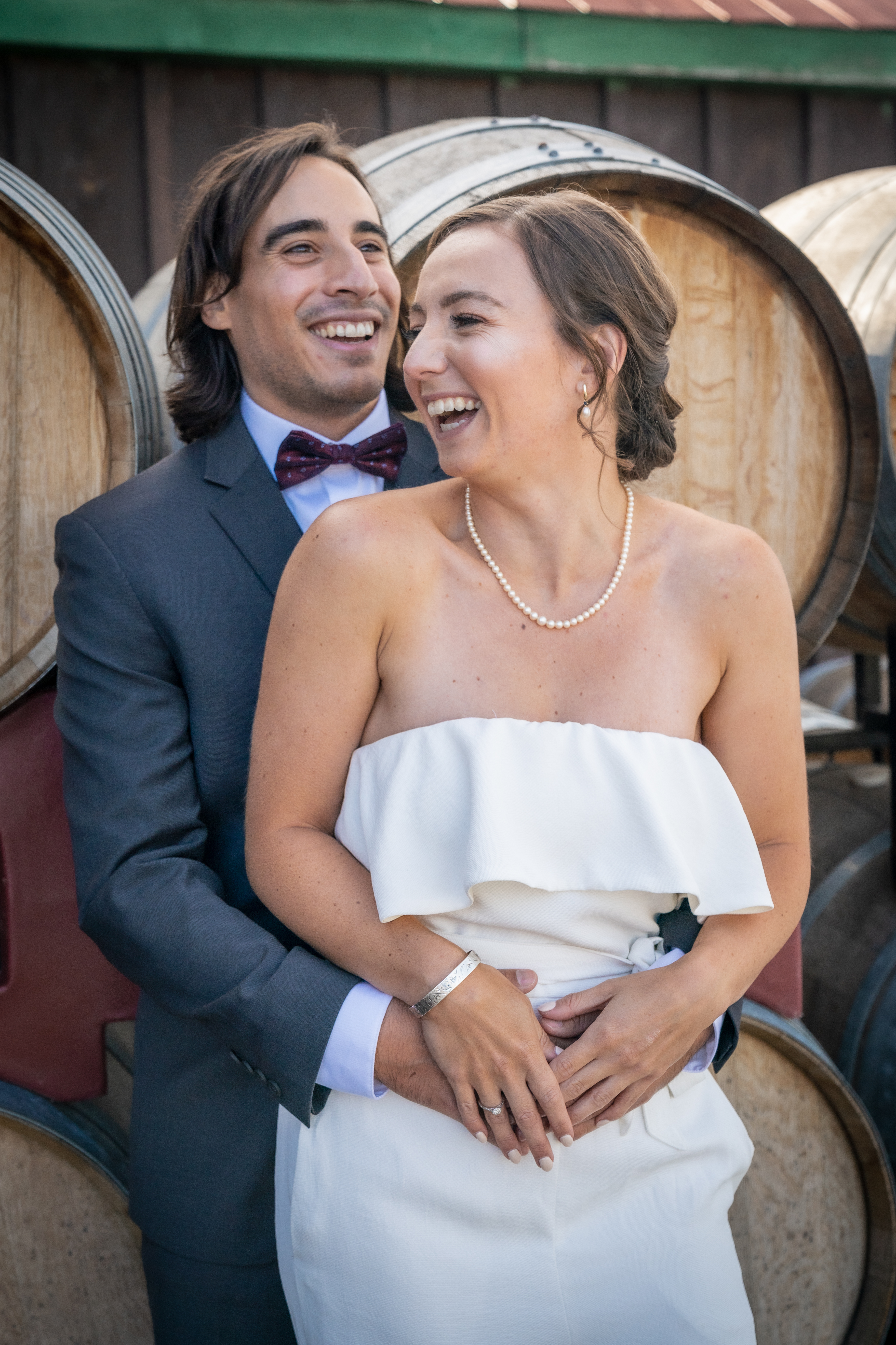 bride and groom laughing in front of wine barrels