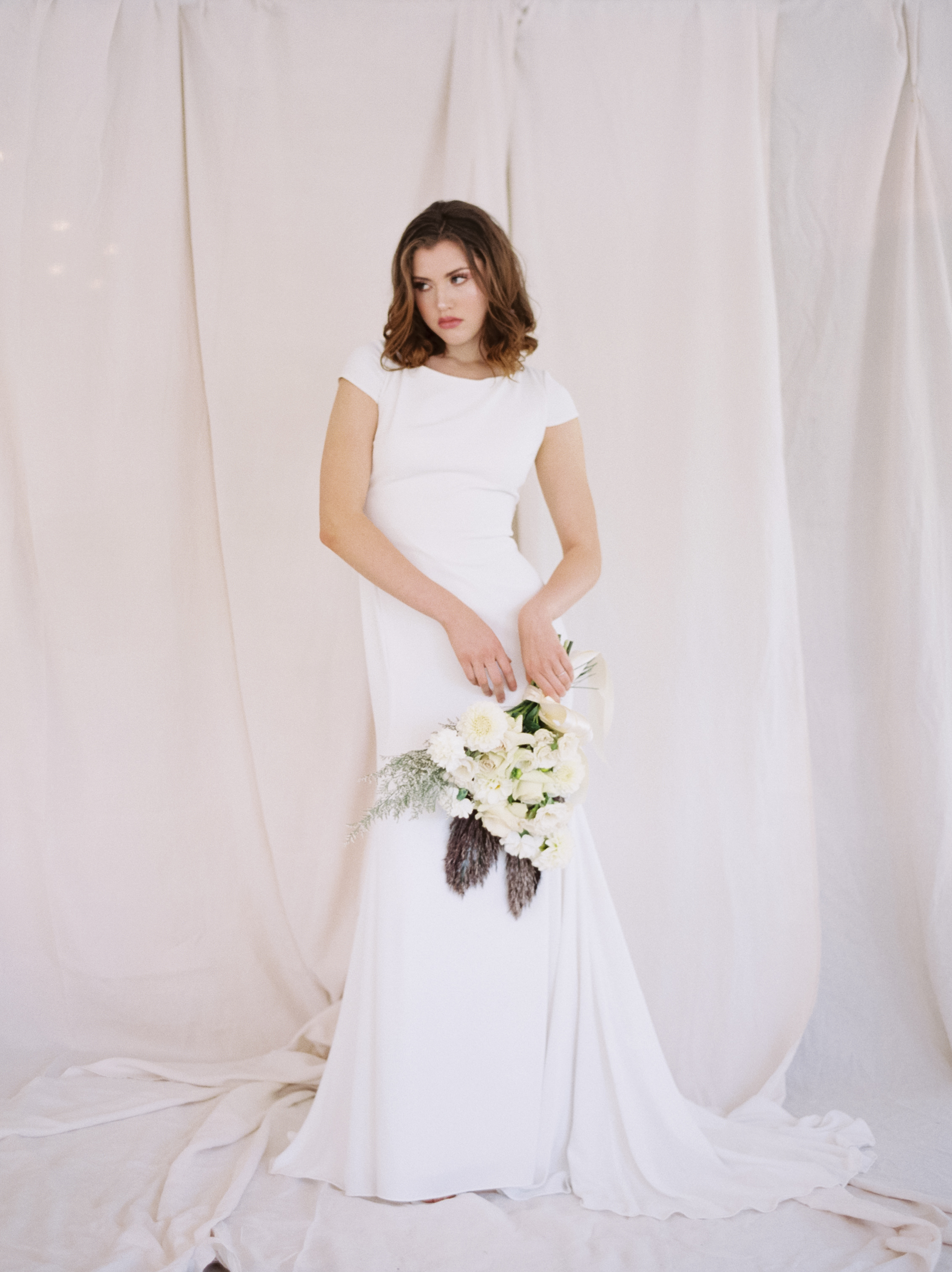 Bride stands with all white florals for editorial shoot