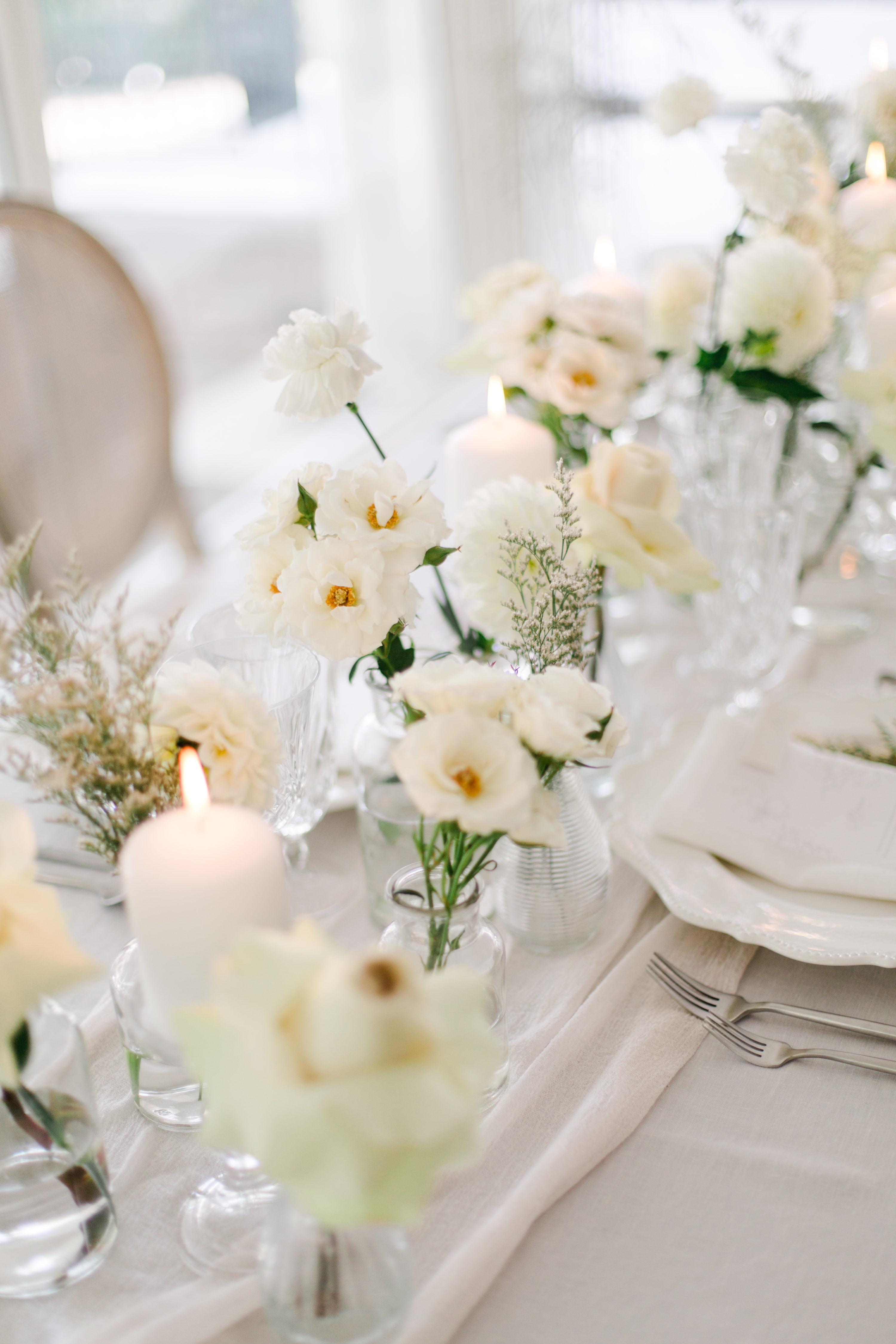 All white wedding table with bud vases filled with white florals