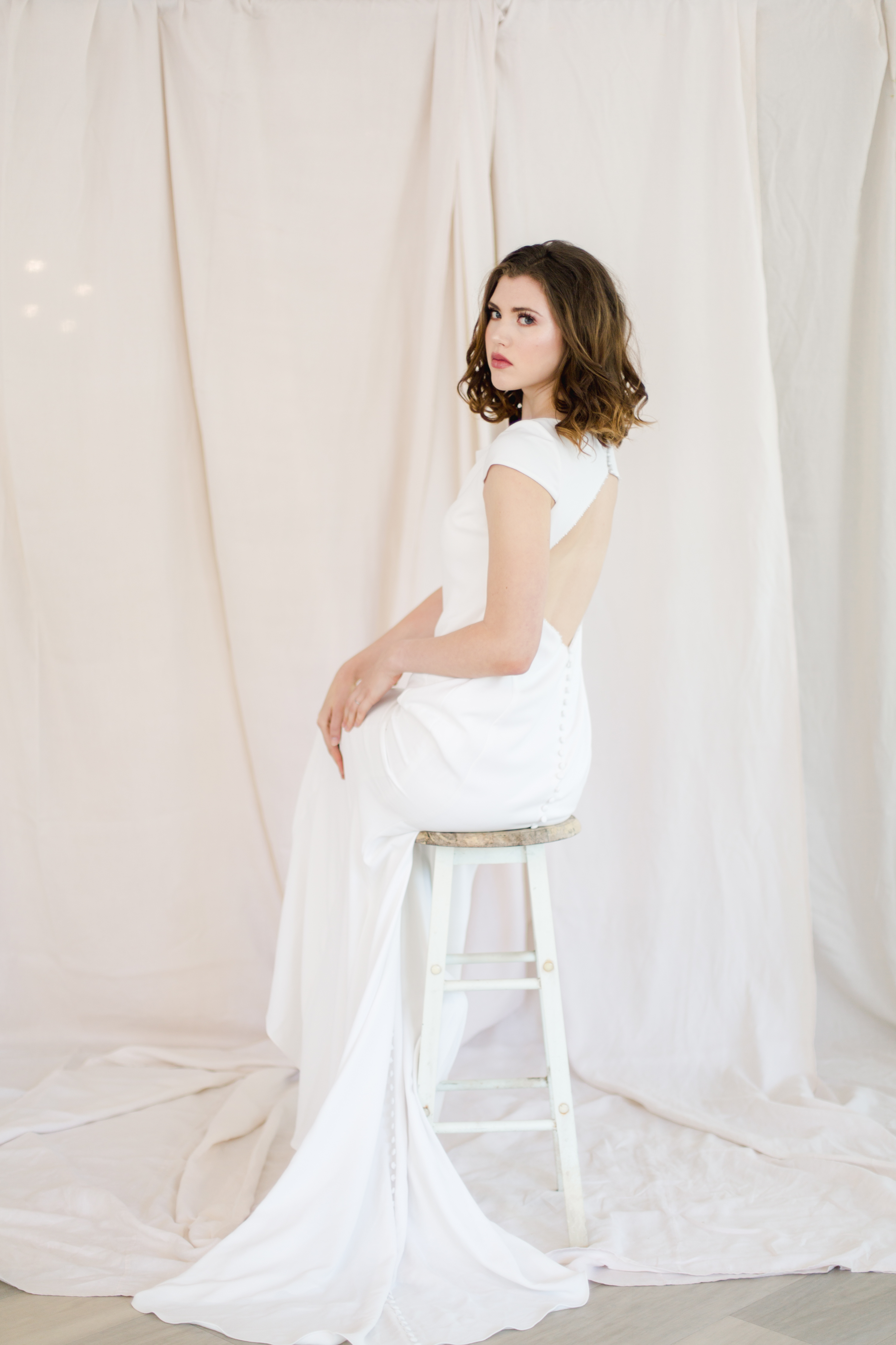 Bride showing off open back dress from Paula's Elegant Bride in St. Catharines